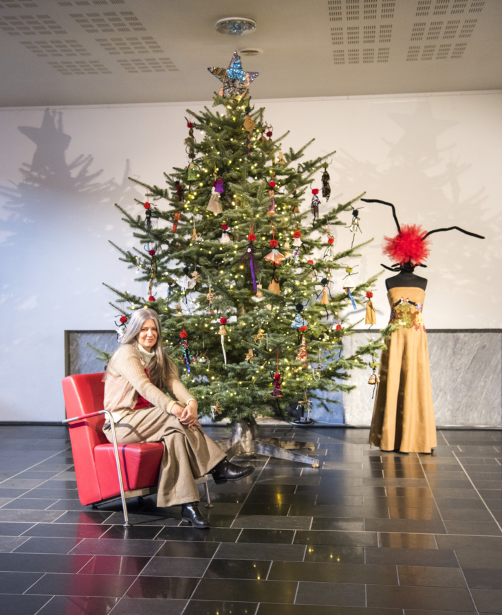"""Julie Skarland in a chair in front of a Christmas tree decorated with small """"Angelinas"""" og a large Angelina next to the tree."""