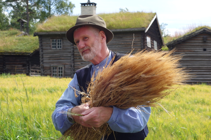 Farmer in old costume at the open-air museum Maihaugen at Lillehammer with a sheaf of grain in his arms.