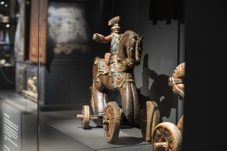 Wooden figure of a rider on a horse with wheels.
