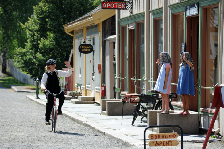 Young man in old costume biking through a steet with painted wood houses waving at two girls at the open-air museum Maihaugen in Lillehammer.