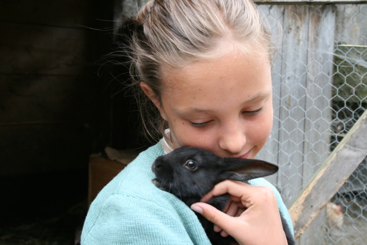 Girl holds a little rabbit to her chest.