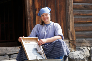 Young woman with headscarf washing clothes on a washboard.