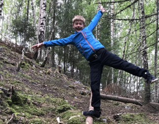 Boy balancing on a lodge in the forest.