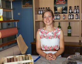 Smiling young woman in old fashioned dress in the historic shop Avlangrud in the open-air museum Maihaugen in Lillehammer.