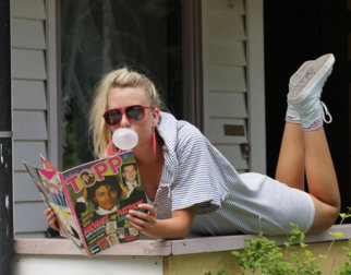 Girl in 1980s cloting with a bubble gum reading a magazine.