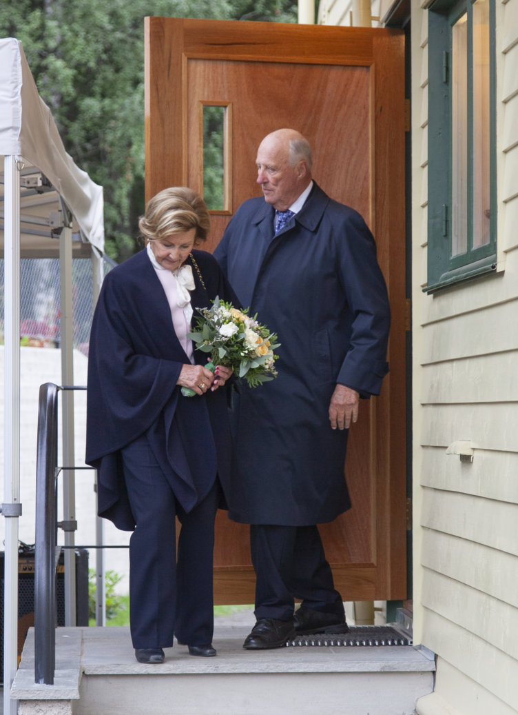 Queen Sonja and King Harald on their way down the stairs from her childhood home.