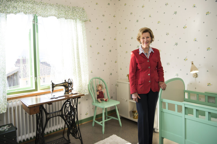 Queen Sonja next to a green painted children's bed.