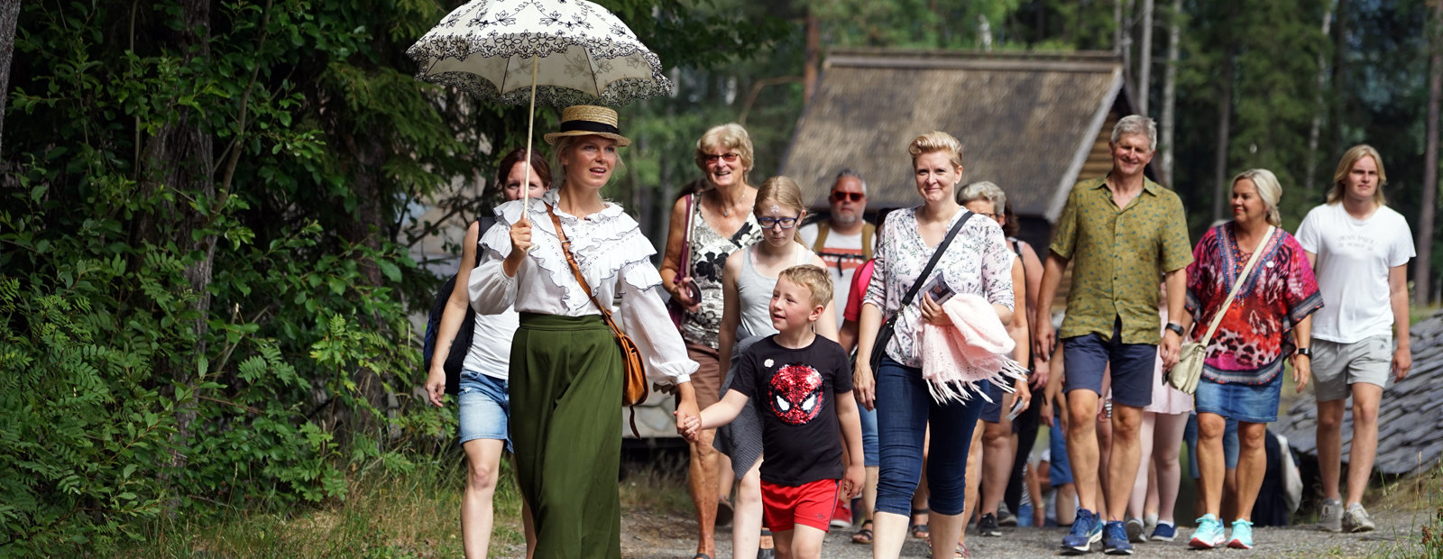 An Engelsk fine lady i historic costume and an umbrella with a group of visitors.